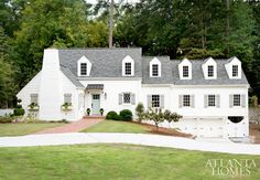 exterior is painted Alabaster by Sherwin Williams on the facade and Pavestone by Sherwin Williams on the shutters.