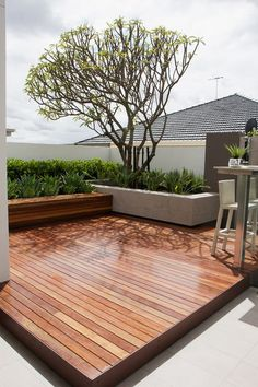 This looks as though it should be a roof terrace. This decked patio is by Tim Davies Landscaping