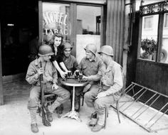 GIs of the 79th Infantry Division enjoy a cold one at a pub in Mantes-la-Jolie, France - August 1944