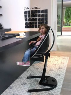 Relaxing in mima moon junior seat. The sleek black model matches this lovely little girl's home perfectly, and moves up and down to suit the height of the dining table or breakfast bar...