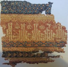 "date uncertain, possibly first half of the 11th c., Egypt, Fatimid period. 6 stitches and 12 rows per cm. The repeated word in Kufic says ""al-Nasr"", ""Victory"". Note 3-strand color knitting at top of piece - dark indigo, medium indigo, and madder red-orange. Documented in ""Tissus d'Égypte. Témoins du monde arabe, VIIIe-XVe siècles : collection Bouvier"", #160."
