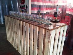 Bar made out of pallets and a plywood top. Screwed together but with hinges on joining bits so it can fold up for storage. Great job!