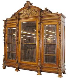 A monumental carved walnut figural three door bookcase.