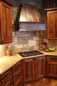 This kitchen is located in Timnath, Colorado and is made from 100 year old reclaimed barnwood with copper detailing on cabinets and range hood. Everything designed and decorated by Roughing It In Style.