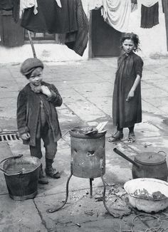 Washday: Two children, their toes poking out of their boots, tend a fire in a battered tin brazier to heat buckets and bowls of water in which to scrub clothes. The clean garments would be hung on lines strung across the street