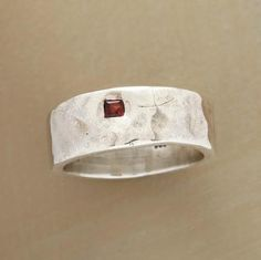 A hammered square setting in a sterling silver band surrounds the bright light of a single red garnet. Handcrafted for Sundance. Whole sizes 5 to 9.