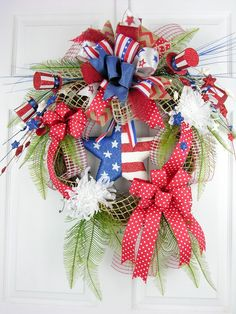 It's all here in this patriotic embellished grapevine wreath. A glittered star takes center stage surrounded by ferns, star picks and Uncle Sam hats. Textured burlap windowpane ribbon with a large Ter