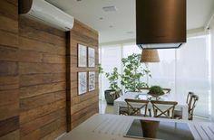 Detalhe da climatização da sacada, bancada em Corian com fogão de mesa elétrico, coifa moderna e mesa de refeições quadrada. Painel em madeira de demolição com iluminação direcionada.