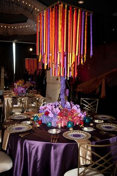 moroccan themed wedding table decor… purple and gold with multicolored light streams over top of table decorum… Photographer: Shawna Herring Photography, Atlanta, GA… venue location:W Midtown Hotel, Atlanta, GA