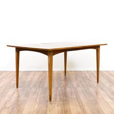 This mid century modern dining table is featured in a solid wood with a teak finish. This dining table has tapered legs, curved trim and a a striped wood table top. Stylish table perfect for a small dining room! #midcenturymodern #tables #diningtable #sandiegovintage #vintagefurniture
