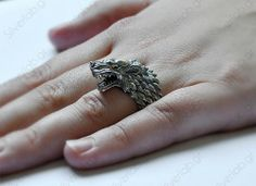 Game Of Thrones House Stark Direwolf Ring  Forged out of fine sterling silver, this ring depicts the House Stark house symbol, the direwolf. With 14k gold eyes and a detailed head, this ring is a sure eye-catcher. Sold on Etsy.