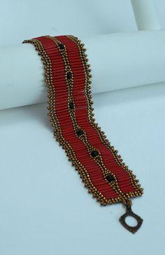 Élégant bracelet à laide des éléments dans des tons bronze, rouge et noir. Perles de bugle lustre scintillant alignent de chaque côté de 4mm ronde perles de verre et perles de rocaille. Petites perles bronze japonais complet le thème ! Jai utilisé des chevrons technique pour faire ce bracelet, qui donne un aspect onduleux élégant. Fermoir toggle ton bronze antique ferme le bracelet. La longueur est 7 1/2 pouces avec fermoir La largeur est 1 1/2 pouces Veuillez mesurer votre poigne...