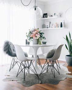 Dining Room decor ideas - small modern style dining with white and grey color palette.  White round table, Eames chairs, cowhide rug, floating shelves and glass orb light fixture featuring   oh.eight.oh.nine