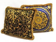 Versace pillows, comprising: (1) black Baroque style with gold scrolled foliate and medusa head center,; (1) Versace Atelier royal blue with gold foliage decoration and medusa head