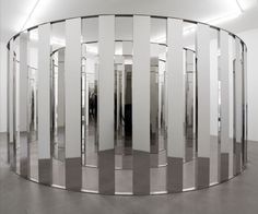 "Artists Johann Koenig: ""Two curved lines of mirror lamellae placed equal distances apart create a spiral structure similar to a snail's shell. The installation can be entered from both sides, as the distance between the lines offers enough space to walk along the spiral labyrinth."""