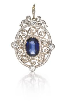 A Fabergé jewelled gold pendant, Moscow, 1899-1908, the oval sapphire claw-set within an openwork rose-cut diamond-set scroll frame and four large circular-cut diamonds, ribbon surmount.