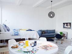 Cama elevada, piso em madeira clara, mesa ampla.