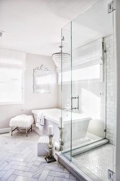 Beside a seamless glass shower, a Pottery Barn Clarissa Crystal Drop Round Chandelier hangs over a rectangular freestanding pedestal bathtub placed on marble herringbone floor tiles.