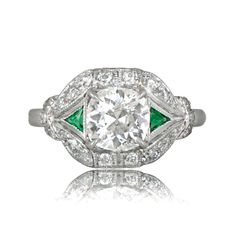 Accented by aemeralds on either side, sits a prong-set antique old European cut diamond. The diamond studded handcrafted platinum mounting is adorned with filigree and milgrain, and furtherembellishedwith diamonds on the shoulders.The center diamond was cut circa 1920, and was graded by our gemologist as weighing 1.18 carats, having a J color and a clarity of VS1.The ring is currently a size 7, but it can be sized up or down by our in-house jewelers, at no extra cost.