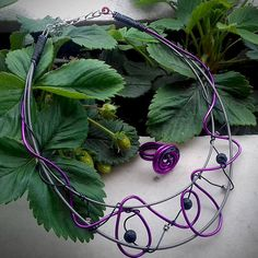 A necklace made out of bass guitar strings, beads and purple wire! It is accompanied by a matching ring. Code: 211
