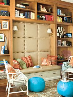 The upstairs landing of this Covington, Louisiana home was transformed into a small den that makes an inviting, casual family hangout. An upholstered wall softens the space above the built-in bench, while bamboo Chippendale-style chairs and vibrant turquoise Moroccan poufs add plenty of extra seating. (Photo: Laurey W Glenn)