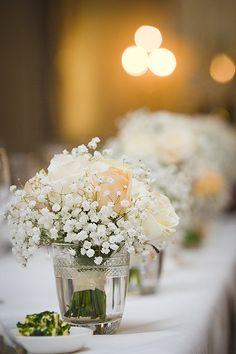 What about small bunches of flowers (3 vases per table) of roses & baby breath with 3 candle votives