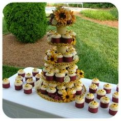 Sunflower cupcake tree - This is a cupcake tree i made for my baby brother's wedding rehearsal dinner.  The tree if made from6-8-10-12 cake drums and th bottom is a 15 in masonite cake board (to make it not topple over). I covered them with shelf liner and the middle part is pvc pipe covered in shelf liner.  the topper I made myself. The cupcakes are baked int he nut paper holders that wilton sells and then wrapped in a piece of scrapbook paper.  I made the sunflowers on the cupcakes too.