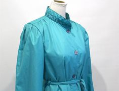 👗 • 👔 • 👠 Vintage 1970's teal sea-foam coloured trench coat. Single breasted buttons, with wrap belt. Stunning mandarin-style collar.  Material is in excellent condition, shiny and bright shade. Custom-made coat — Sterling Stall — —Made in Winnipeg, Canada — Outer Shell: Polyester