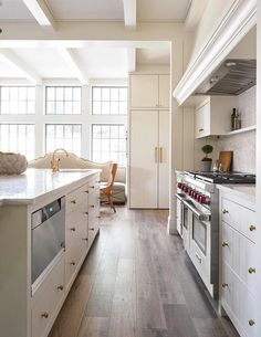 An off-white kitchen island is fitted with plank drawers and a microwave alongside a prep sink.