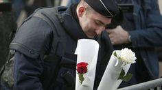 Ein Polizist legt Blumen an der Veranstaltungshalle Bataclan nieder.  Charles Platiau