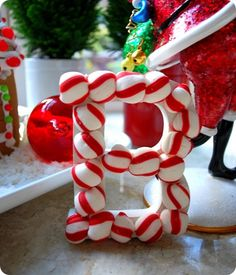 You can create these with some $1 dollar craft store letters, craft glue and soft peppermints. To create, simply cut peppermints in half, shave with fine grater to make perfectly flat on rear, then secure with craft glue for a whimsical monogram. Good craft for kids, or make JOY for the kitchen, kids' names to hang on the tree, etc.