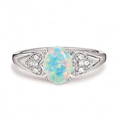 84313186e27b4 Sterling silver openwork ring with an oval simulated opal in the center. CZ  embellished hearts are on either side of the center stone.