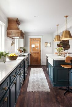 Warm details, like the vent hood, the brass pieces, and the antique doors leading to the music room and laundry room make the space feel finished. #interiordecorstylesjoannagaines