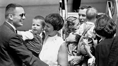 Mark Armstrong reaches out to attract his dad's attention after Gemini 8 spacecraft pilots Armstrong and Scott arrived back home in Houston, on March 21,1966. Mrs. Armstrong holds the youngster as Donald K. Slayton, assistant director of Manned Spacecraft Center flight crew operations, waits to congratulate Armstrong.