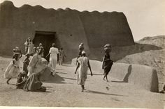 Nigeria, view of Kano gate. Gate through what appears to be a city wall. Male and female adults and children walking along road in front of gate, some carrying containers on heads. Medium: Gelatin silver print.