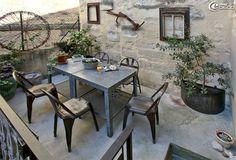 Equipement d'une terrasse à Uzès décorée par Esprit d'Uzès : anciennes tables de rempotage en métal galvanisé, chaises de jardin en métal, vasistas de récupération et vieux cadre de mobylette accrochés au mur