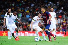 Neymar of FC Barcelona duels for the ball with among players of Santos during a friendly match between FC Barcelona and Santos at Nou Camp on August 2, 2013 in Barcelona, Spain.