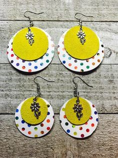 A pair of circle earrings for mother and daughter. The bottom layer is multicolored and the top layer is yellow suede. A silver flower charm adorns the earrings. Moms earrings are 2inches round and 1 1/2 inches round Daughters earrings are 1 1/2 inches round and 1 inch round All