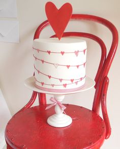 """The cake was inspired by the gorgeous heart bunting pattern on the Kikki K wrapping paper and the heart pattern found on most of their Valentine cards. It is actually a very simple cake, A clay extruder was used to create the red """"string"""" and edible paper to create the hearts."""