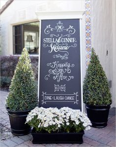 chalkboard wedding sign by topiaries and white flower arrangement (chalkboard paint on with moulding & put on stand?) Have huge 6 foot black frame already (repaint it?) and write a welcome to guests entering #diy gifts| http://diy-gifts.kira.lemoncoin.org