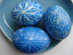 The artist is using a blue monochromatic color scheme. I know this because the entire photograph is blue. Describe one of the designs in the eggs