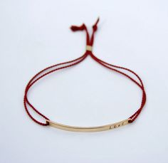 Skinny bar LOVE bracelet with silk cord - Nameplate bracelet with tiny font - Cord bracelet - 14k gold fill or sterling silver by shopLUCA on Etsy https://www.etsy.com/listing/209655838/skinny-bar-love-bracelet-with-silk-cord