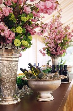 An impeccably arranged champagne bar rests between two metallic urns filled with colorful fresh florals. Wild flowers in champagne buckets! Champagne Bar, Champagne Buckets, Champagne Breakfast, Vibeke Design, Engagement Celebration, Deco Floral, Decoration Table, Event Decor, Punch Bowls