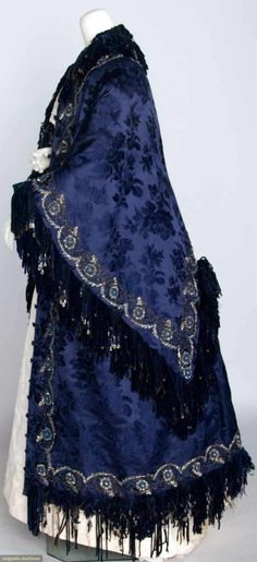 "SILK JACQUARD LONG CAPE, c. 1888 Augusta Auctions November 13, 2013 - NYC New York City Floral pattern in sapphire blue, cape & undercape trimmed w/ cut steel beads & blue silk chenille fringe, French label, L 50.5"", (minor bead loss, some breaks in chenille)."