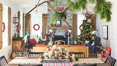 Living room and adjoining dining room with Christmas decorations, including wreaths, fireplace mantel decor, large Christmas tree and a holiday centerpiece.
