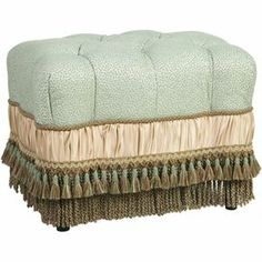 """Showcasing sumptuous button tufting and tassel accents, this charming ottoman makes a chic addition to your living room or master suite.     Product: OttomanConstruction Material: PolyesterColor: MultiFeatures:  Bullion, braid and tassel fringeBrings classic style and luxurious comfort to the home Dimensions: 17.5"""" H x 22"""" W x 17"""" D"""
