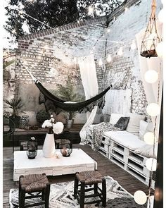 Perfect patio terrace porch for parties or lounging. Tall whitewashed brick wall for privacy and ambiance. Hammock and palette furniture to lounge in on the wooden wood deck. Home design decor inspiration ideas.