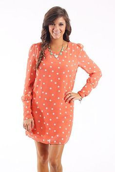 "The Mary Jane Dress, Melon $41.00 This dress is beyond lovable! We love the sweet and simple design of the polka dots! This dress is fully lined and features a cuffed sleeve with five small buttons and a criss-cross design at the top of the back.   Fits true to size. Miranda is wearing a small.   From shoulder to hem:  Small- 31""  Medium- 32""  Large- 33"""