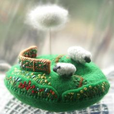 A pin-cushion hill with two sheep, a little fence, and lots of flowers. Above floats a fluffy cloud._ Lambkin Hill by Sakoran