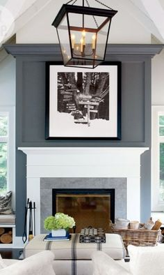 To break up a big blank wall, the client painted the two-story fireplace wall dark gray. The color was a few shades darker than the main wall color. This instantly helped to break up the empty wall space. It created a dramatic focal point and grounded the large open space.
